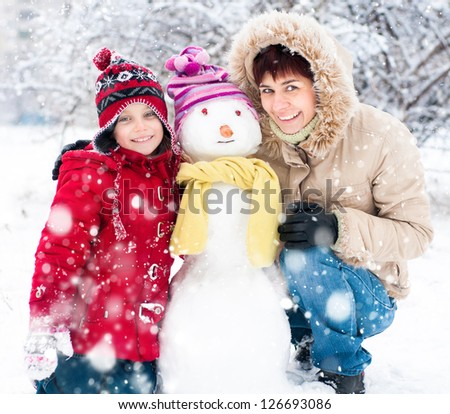 Happy mother and daughter with snowman winter portrait - stock photo