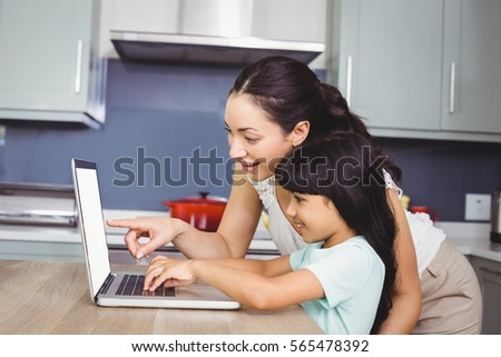 Happy mother and daughter working on laptop at home