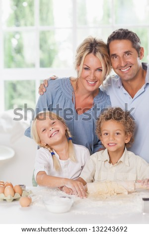 Happy mother and father baking with their children in the kitchen - stock photo