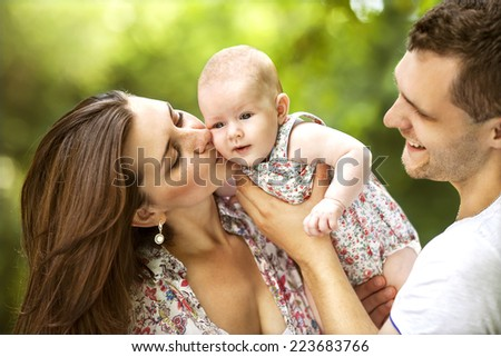 happy mother and father with baby in park - stock photo
