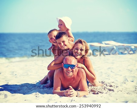 Happy mother and father with three children lying on the sunny beach.