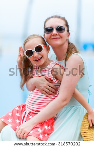 Happy mother and her adorable little daughter outdoors near a swimming pool at tropical resort