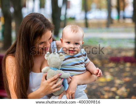Happy mother and her baby-boy on hands play keeps teady bear toy outdoors in park. - stock photo