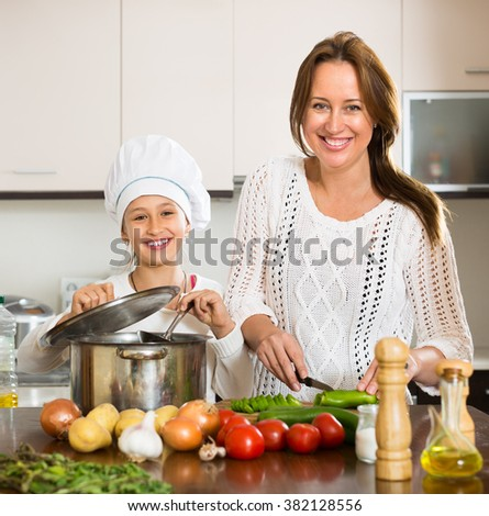 Happy mother and her cheerful daughter in cookersâ??s hat preparing soup together. Focus on girl - stock photo