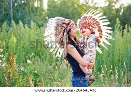 Happy mother and her child playing indians outdoors. - stock photo