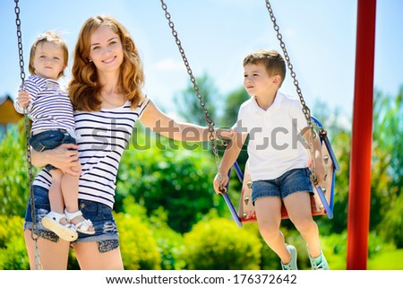 Happy mother and her children on playground - stock photo