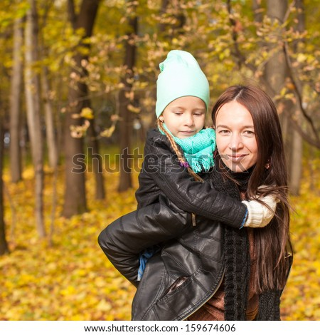 Happy mother and her cute daughter walking in yellow autumn forest on a warm sunny day - stock photo