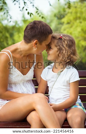 Happy mother and her cute little daughter sitting on a bench in nature. - stock photo