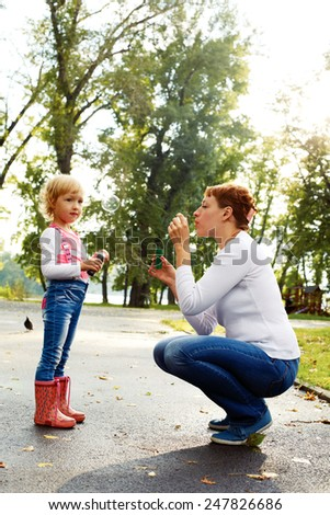 happy mother and her daughter blowing soap bubbles on a warm summer day - stock photo