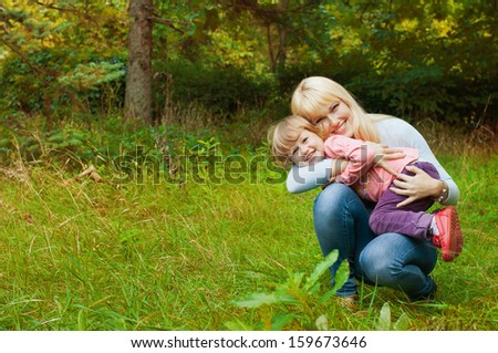 Happy mother and her daughter having fun outdoors