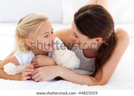 Happy mother and her daughter playing together lying on a bed - stock photo