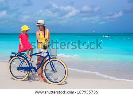 Happy mother and her daughter riding bicycles on a tropical beach - stock photo