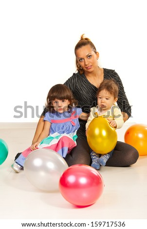 Happy mother and her kids sitting down on floor with balloons - stock photo