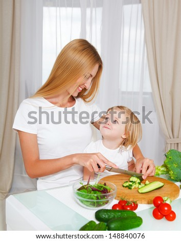 Happy mother and her little daughter cutting vegetables in the kitchen - stock photo