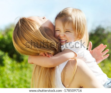 Happy mother and her little daughter in the spring day - stock photo