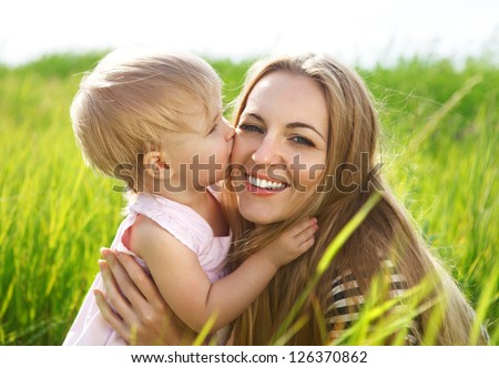 Happy mother and her little daughter in the summer field - stock photo