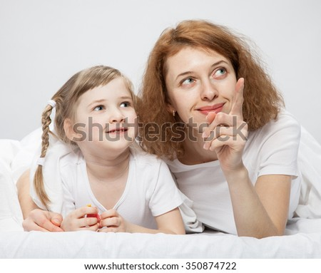 Happy mother and her little daughter playing in the bed, neutral background - stock photo