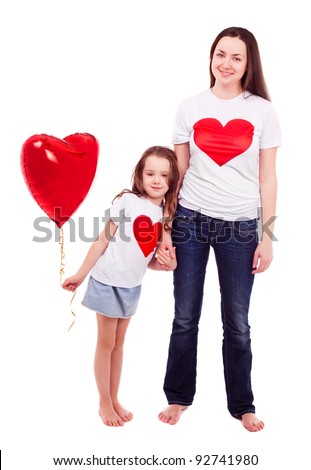 happy mother and her six year old daughter wearing T-shirts with big red hearts and holding a heart-shaped balloon, isolated against white background - stock photo