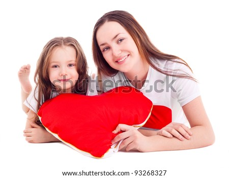 happy mother and her six year old daughter with a heart-shaped pillow, isolated against white background - stock photo