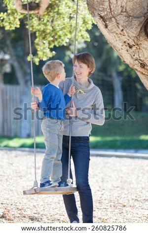 happy mother and her son having fun swinging in the park, mother's day concept - stock photo