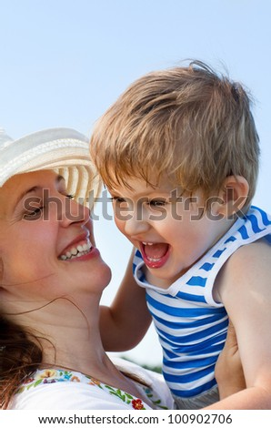 happy mother and her son on blue sky background - stock photo