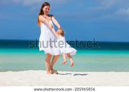 Happy mother and his little daughter at tropical beach having fun during family summer vacation - stock photo