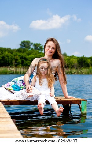 Happy mother and kid sit on an old wooden bridge - stock photo