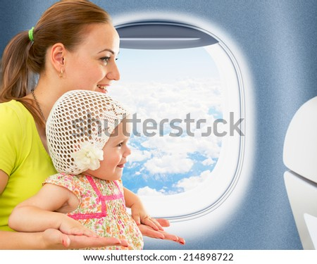 Happy mother and kid traveling together in aeroplane cabin near window
