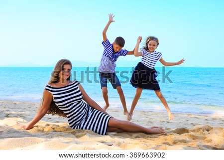 Happy mother and kids, daughter and sun are having rest and playing on the beach, kids are jumping.