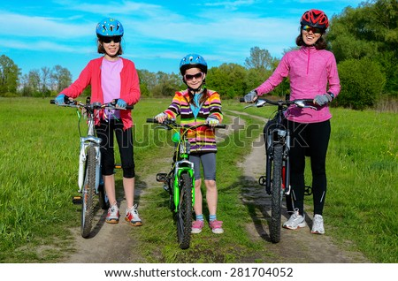 Happy mother and kids on bikes cycling outdoors, active family sport