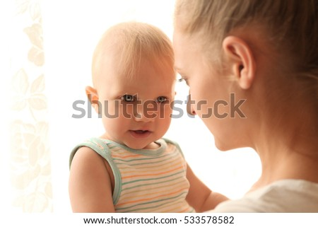 Happy mother and little baby boy on window background