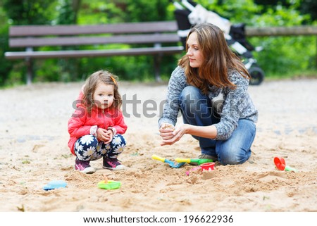 Happy mother and little beautiful daughter playing together on playground in summer