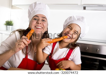 happy mother and little daughter in apron and cook hat eating carrots together having fun at home kitchen smiling playful in healthy vegetable nutrition and education concept - stock photo
