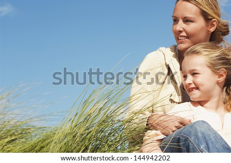 Happy mother and little daughter sitting in long grass against blue sky - stock photo