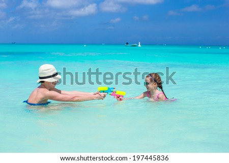 Happy mother and little girl at tropical beach having fun