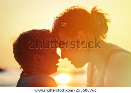 happy mother and son at sunset beach - stock photo