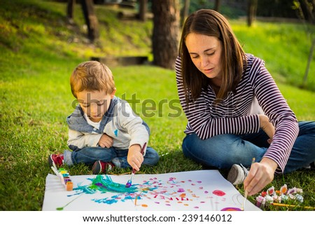 Happy Mother and son child painting in the park. - stock photo