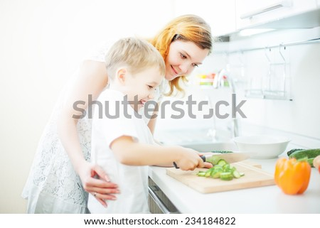 Happy mother and son cooking salad - stock photo