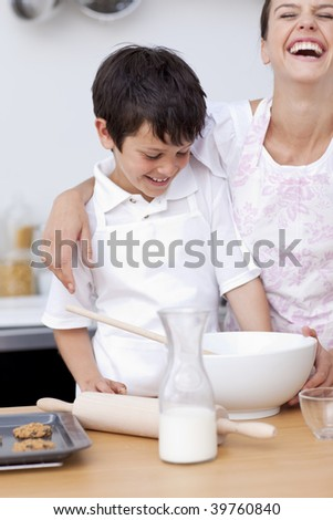 Happy mother and son having fun in the kitchen - stock photo