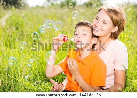 Happy mother and son in the park blowing soap bubbles outdoor portrait - stock photo