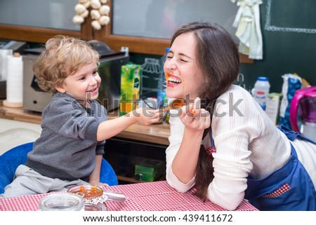 Happy mother and son laughing during breakfast. Little boy is smudging jam on mother's face. - stock photo