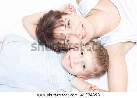 Happy mother and son lying on the bed and smiling - stock photo