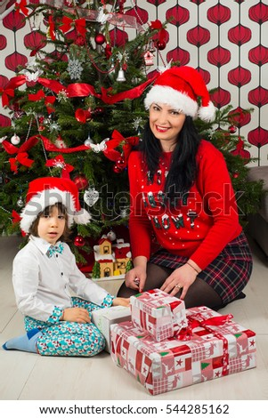 Happy mother and son sitting in front of Christmas tree preparing gifts