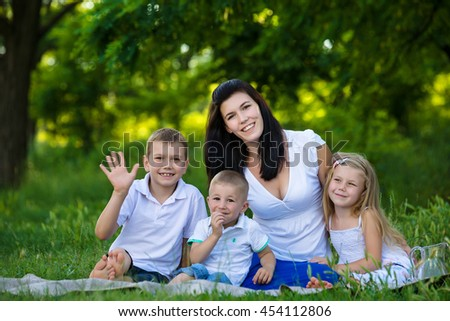 Happy mother and three children at picnic in the park