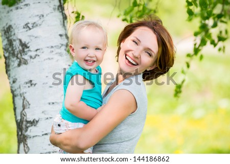 Happy mother and toddler son at field -  outdoor portrait