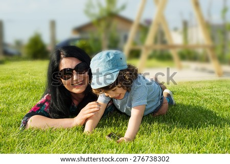 Happy mother and toddler son having fun outdoor on grass in countryside