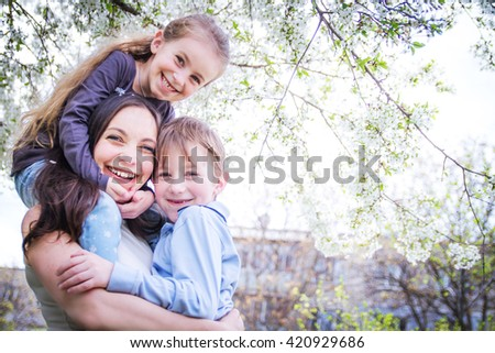 Happy mother and two children hugging among blooming garden