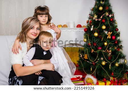 Happy mother and two her children near an decorated fir-tree for Christmas