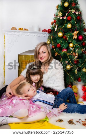 Happy mother and two her children near an decorated fir-tree for Christmas - stock photo