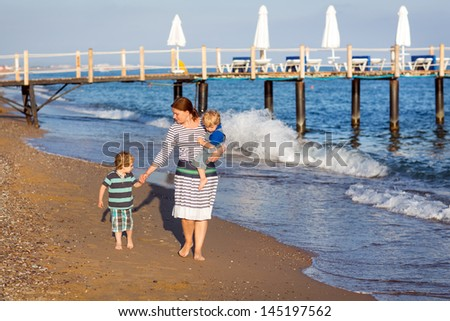 Happy mother and two little children walking on the beach in summer
